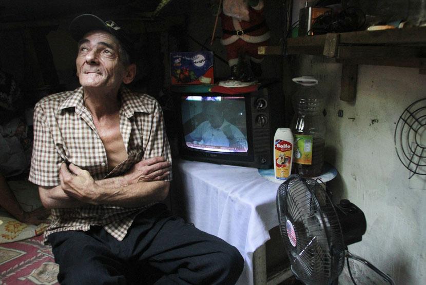 Sebuah pesawat televisi menjadi teman hiburan Miguel Restrepo dalam rumah selokan di kota Medelline,Kolombia, Selasa (4/12). (Reuters/Albeiro Lopera)