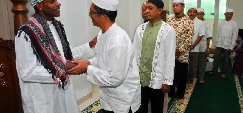 Sejumla warga memberikan ucapan selamat kepada Kepala Suku Asmat, Umar Abdul Kayimter (kiri), yang telah menjadi mualaf di Masjid Darussalam, Jatibening, Bekasi, Jawa Barat, Ahad (19/2).