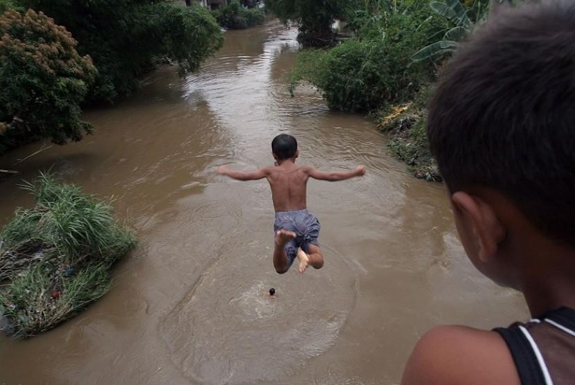 Sejumlah anak bermain dengan melompat dari atas jembatan ke Sungai Deli Medan, Sumut