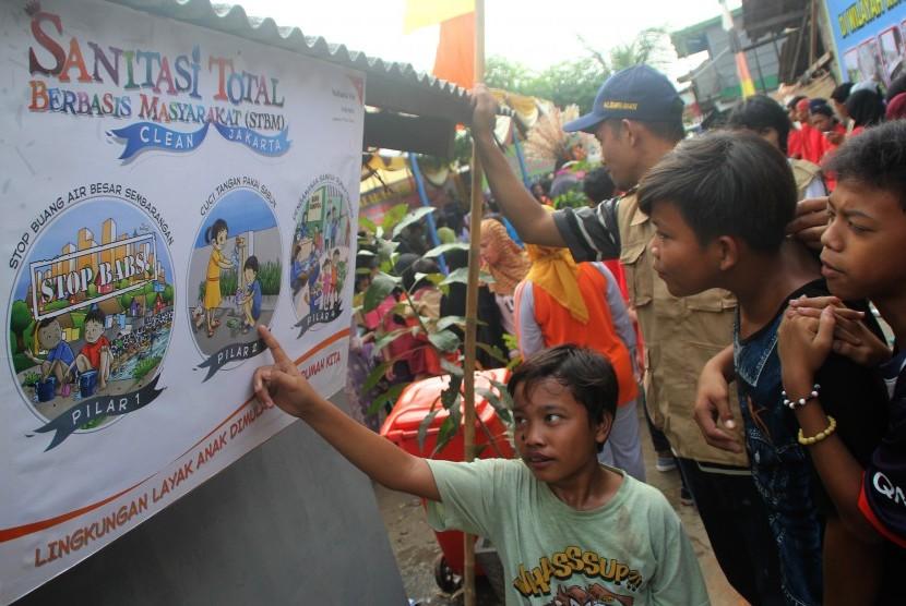 Sejumlah anak menyaksikan poster kebersihan pada saat Deklarasi Stop Buang Air Besar Sembarangan di Kelurahan Semper Barat, Kecamatan Cilincing, Jakarta Utara, Rabu (16/3).