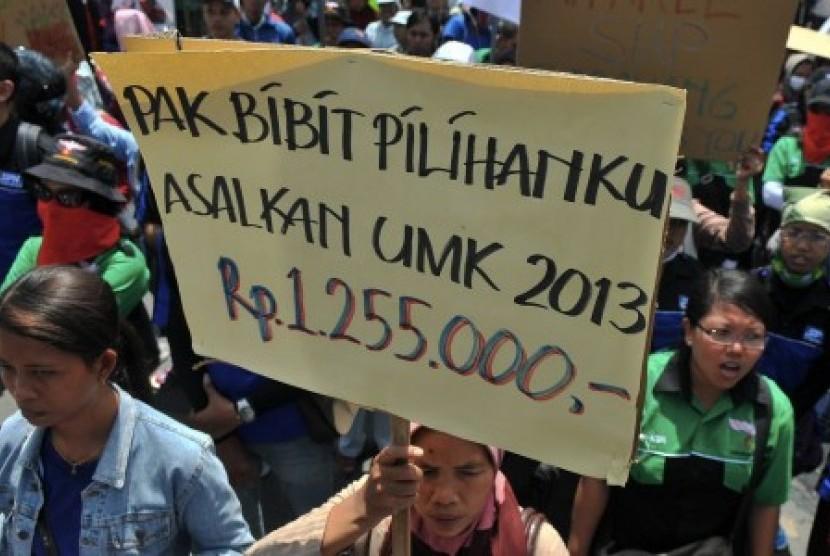 [ilustrasi] Sejumlah buruh membawa poster saat berunjuk rasa tentang usulan upah minimum.
