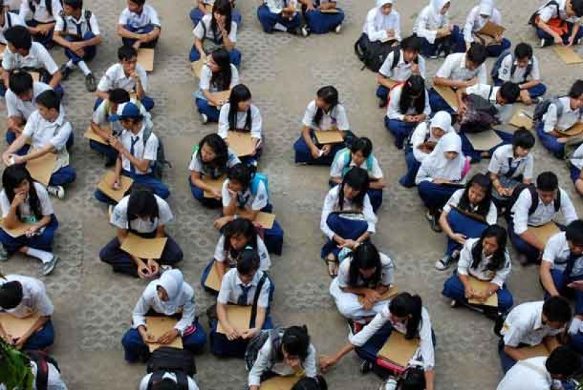 Sejumlah calon siswa duduk di lapangan ketika mengantri untuk daftar di sekolah.  (ilustrasi)