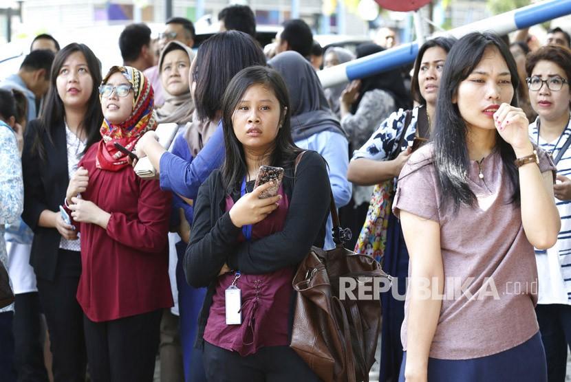 Sejumlah karyawan berkumpul di luar gedung pasca gempa yang mengguncang Jakarta, Selasa (23/1).
