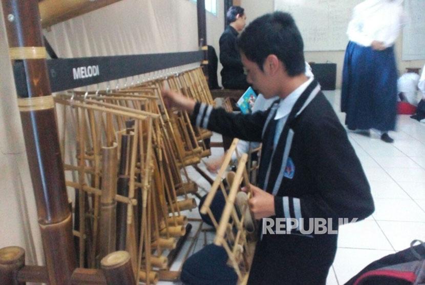 Sejumlah murid SMPN 1 Kota Tasik memilah-milih angklung dalam pelatihan gratis yang digelar oleh sanggar seni Asta Mekar.