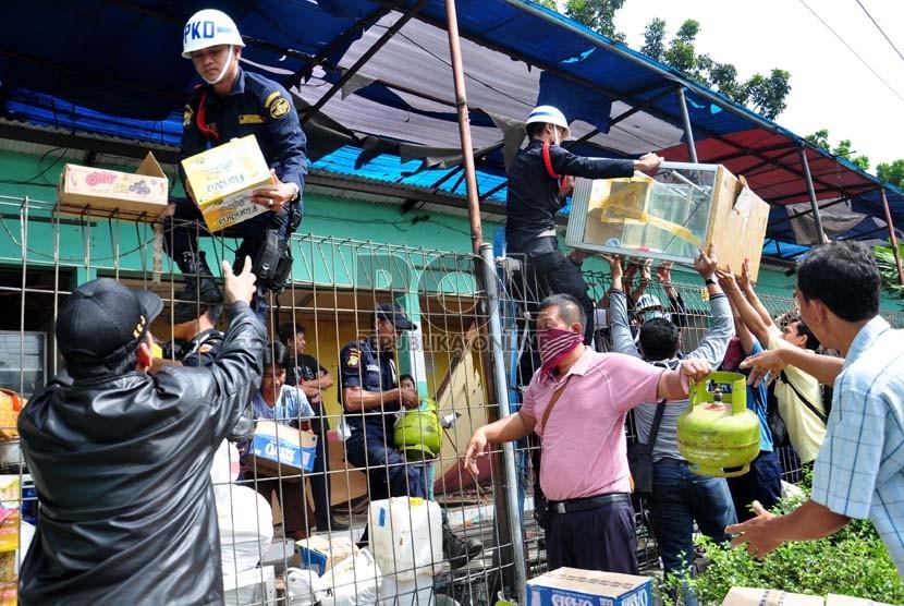 Sejumlah pedagang kaki lima (PKL) dibantu petugas mengangkut barang mereka saat penertiban PKL di Stasiun Pasar Minggu, Kamis (18/4). (Republika/Rakhmawaty La'lang)