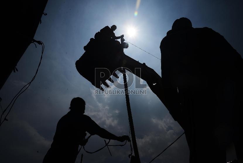 Sejumlah pekerja memperbaiki kabel listrik dengan menggunakan eskavator di Kawasan Pluit, Jakarta Utara, Selasa (20/1). (Republika/Raisan Al Farisi)