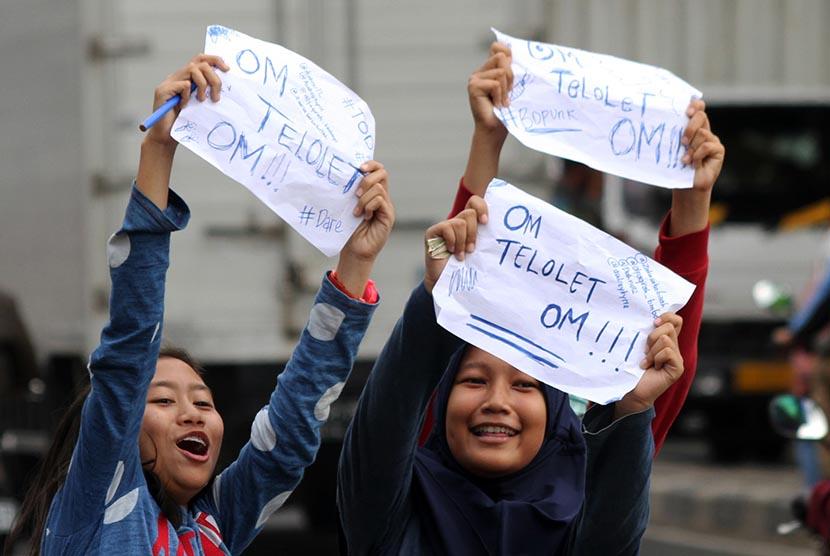 Sejumlah pelajar sekolah menuliskan pesan Om Telolet Om agar pengemudi bus membunyikan klakson di Jalan Sudirman, Bekasi, Jawa Barat, Rabu (21/12).