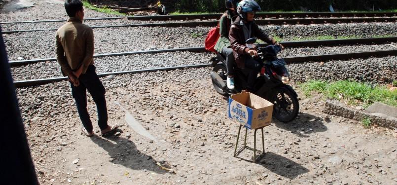 Sejumlah pengendara sepeda motor melintasi perlintasan rel kereta api tanpa palang pintu di Palmerah, Jakarta, Rabu (21/3). (Republika/Agung Fatma Putra)