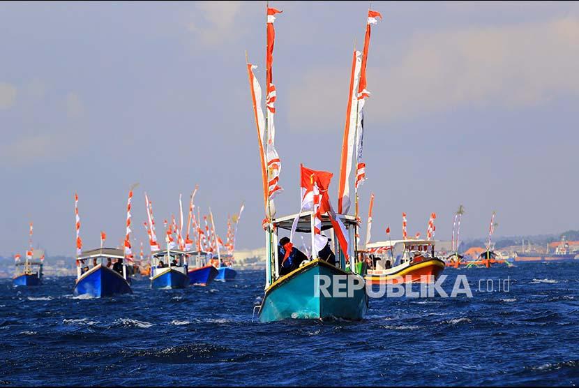 Sejumlah perahu nelayan melakukan parade Kemerdekaan di Pantai Watu Dodol, Banyuwangi, Jawa Timur, Sabtu (12/10). Sebanyak 72 kapal nelayan dan wisata mengikuti Parade Kemerdekaan dalam merayakan HUT Ke-72 Kemerdekaan RI.