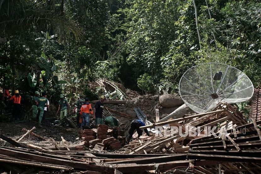 Sejumlah personel Tagana bersama relawan dan warga membersihkan puing rumah, yang roboh terkena longsor di Desa Cihonje, Gumelar, Banyumas, Jawa Tengah, Senin (18/12).