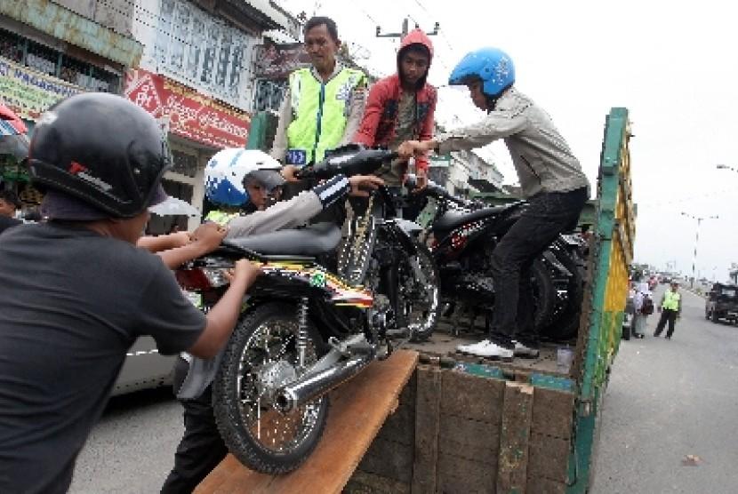 Sejumlah petugas mengangkut sepeda motor milik siswa yang tidak memiliki surat kendaraan ke dalam bak truk saat razia geng motor.