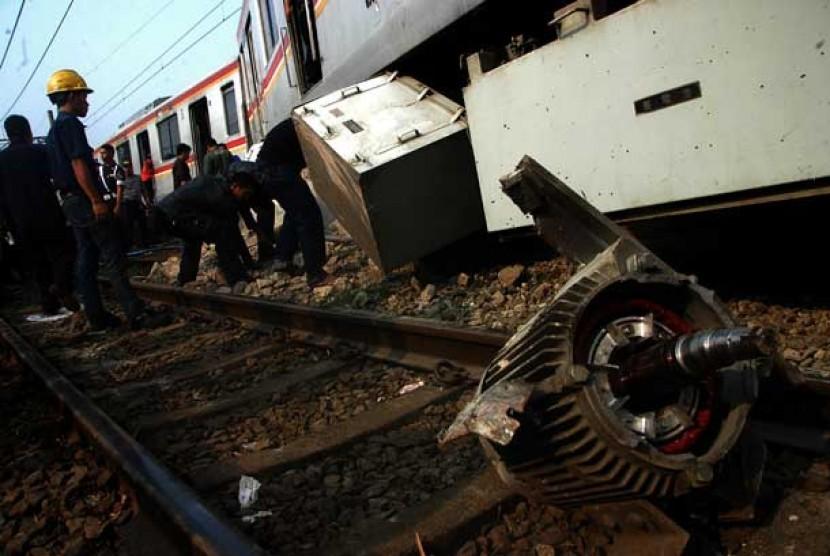 Sejumlah petugas mengevakuasi gerbong KRL Commuter Line Jurusan Bogor-Jakarta Kota yang anjlok dan menabrak pembatas rel di Stasiun Cilebut, Bogor,Kamis (4/10).