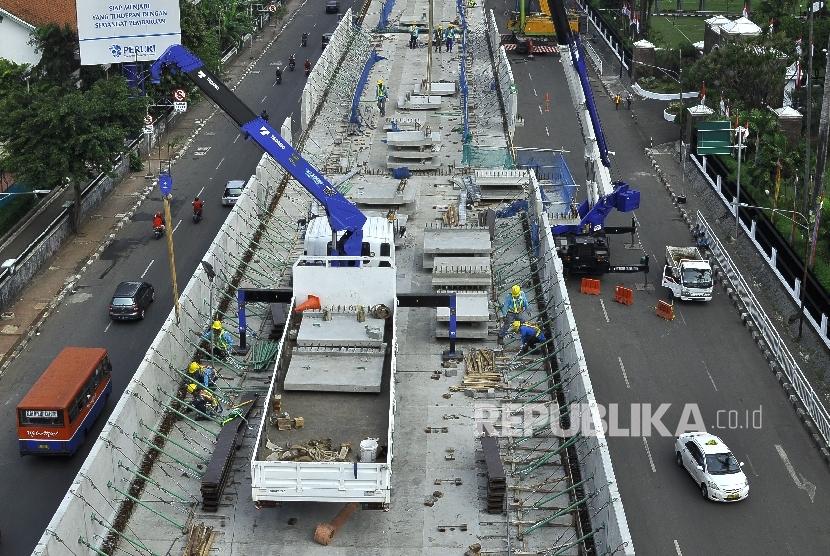 Sejumlah petugas menyelesaikan proyek pembangunan moda transportasi massal, Mass Rapid Transit (MRT) di Jalan Kyai Maja, Jakarta Selatan, Ahad (9/7).