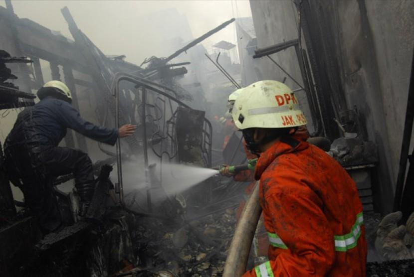 Sejumlah petugas pemadam kebakaran berusaha memadamkan sisa api yang masih menyala ketika terjadi kebakaran di kawasan Jalan Kartini, Jakarta, Senin (27/8).