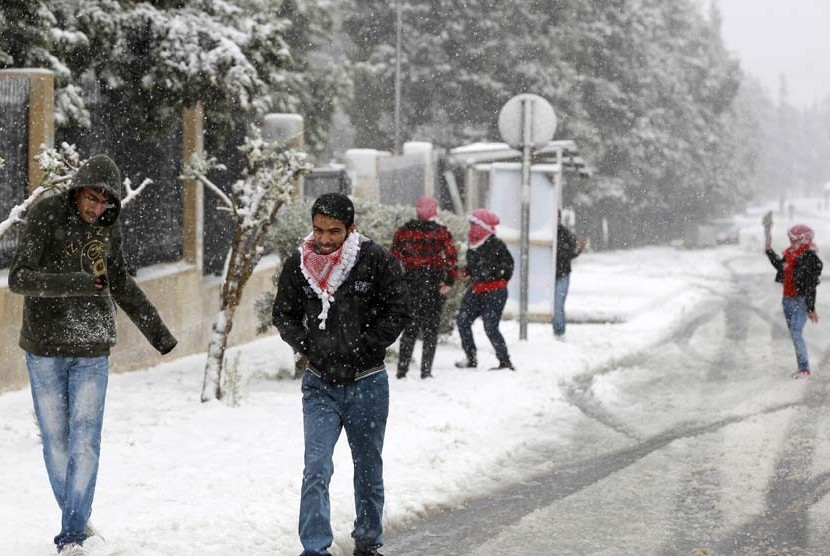 Sejumlah pria bermain salju setelah badai salju menerpa kota Amman,Yordania, Rabu (9/1).  (Reuters/Muhammad Hamed)