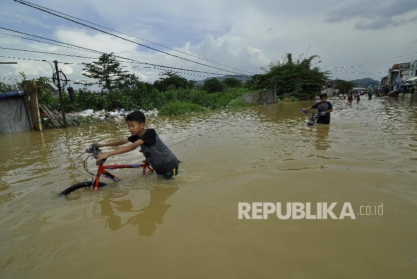 Sejumlah remaja menerobos banjir yang merendam di Jalan Raya Banjaran di Kelurahan Andir, Kecamatan Baleendah, Kabupaten Bandung, Rabu (8/3).