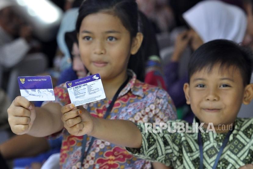Sejumlah siswa menunjukan Kartu Indonesia Pintar sebelum kedatangan Presiden Republik Indonesia Joko Widodo (Ilustrasi)