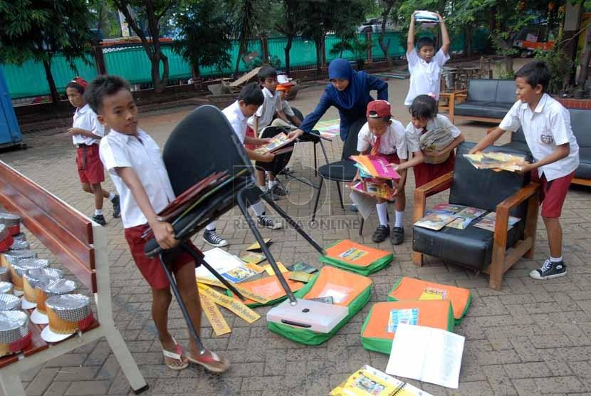 Sejumlah siswa merapihkan perlengkapan sekolah di halaman SDN 02/03