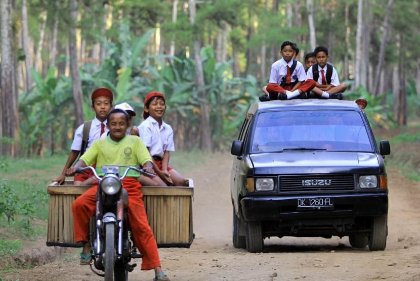 Sejumlah siswa sekolah dasar berangkat ke sekolah menaiki mobil angkut dan motor di Jayengan, Banyuwangi, Jawa Timur. (ilustrasi)