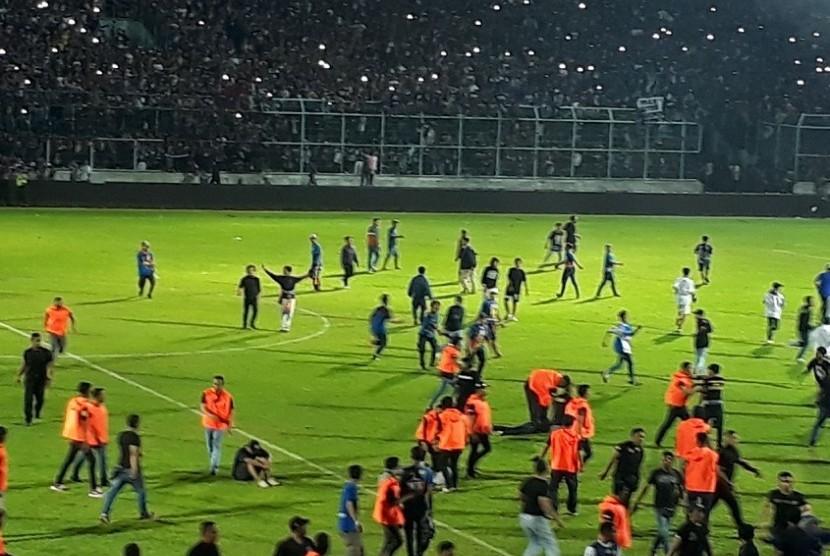 Sejumlah suporter Arema FC memasuki lapangan Stadion Kanjuruhan menjelang berakhirnya laga Arema FC vs Persib Bandung, Ahad (15/4).
