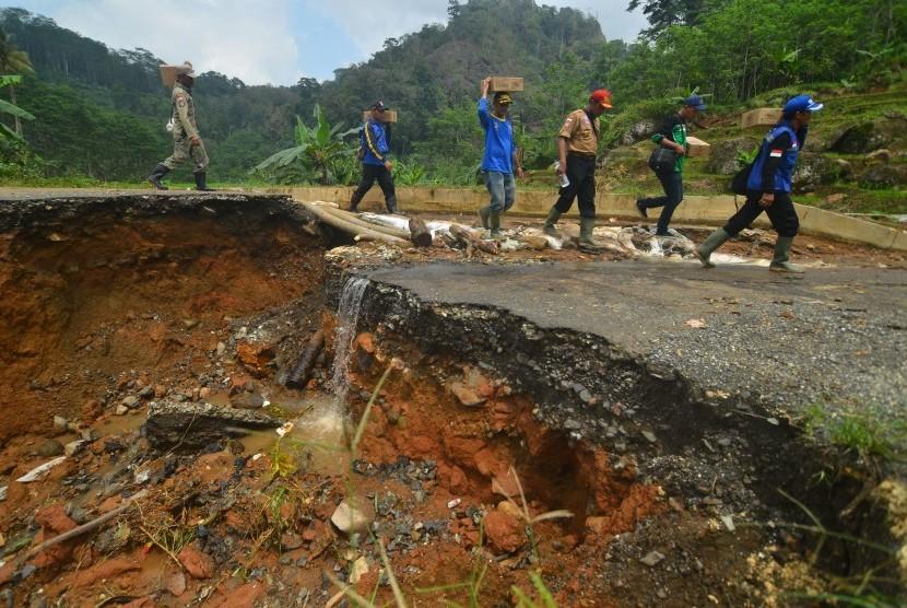 Sejumlah Taruna Siaga Bencana (Tagana) berjalan di sekitar jalan yang ambles saat membawa bantuan untuk korban longsor dan pergerakan tanah di Desa Kalijati, Kabupaten Pangandaran, Jawa Barat, Ahad (8/10).