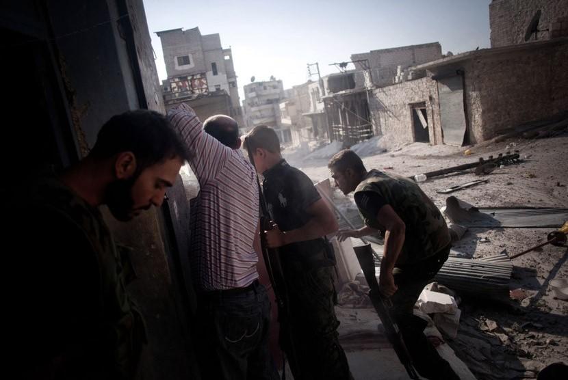 Seorang Tentara Pembebasan Suriah berjalan melalui sebuah jalan di distrik Amariya di Aleppo, Suriah, Senin (10/9).    (Manu Brabo/AP)