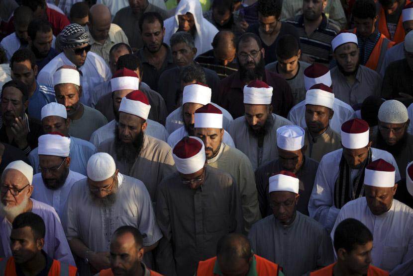 Sejumlah ulama pendukung Presiden Muhammad Mursi melaksanakan Shalat Idul Fitri sampai keluar jalan raya di luar Masjid Rabaah al-Adawiya, Nasr City, Kairo, Kamis (8/8).  (AP/Khalil Hamra)