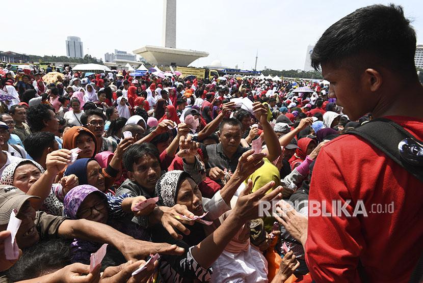 Sejumlah warga berdesakan untuk mengambil sembako gratis saat acara Untukmu Indonesia di kawasan Monas, Jakarta, Sabtu (28/4).