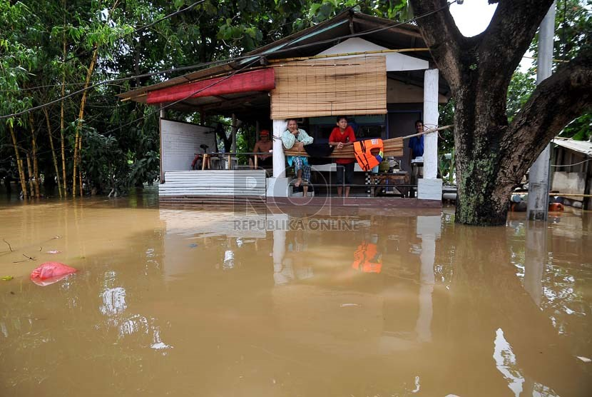 Sejumlah warga bertahan di lantai dua rumahnya yang terendam luapan air Sungai Ciliwung di Jalan H Bawah, Kelurahan Kebon Baru, Kecamatan Tebet, Jakarta Selatan, Rabu (22/1).  (Republika/Prayogi)