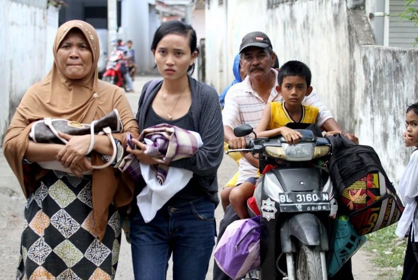 Sejumlah warga Kampung Jawa Lama berlarian keluar rumah menyelamatkan diri setlah mendengar isu tsunami pasca gempa melanda Lhokseumawe, Provinsi Aceh. Rabu (11/4).
