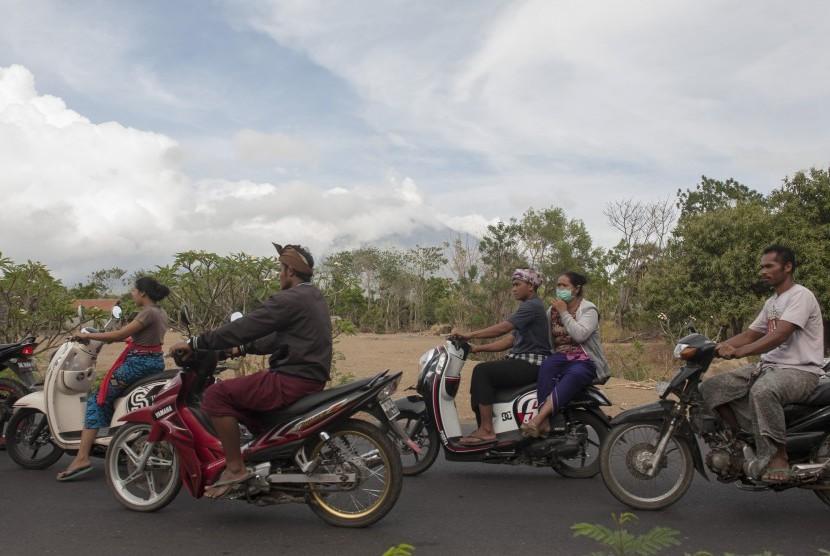 Sejumlah warga melintas di jalan Desa Datah yang berjarak sekitar 10Km dari kawah Gunung Agung, Karangasem, Bali, Minggu (8/10).