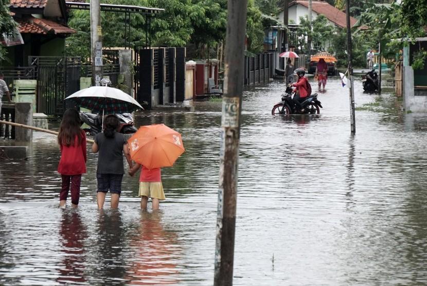 Sejumlah warga melintasi banjir, ilustrasi