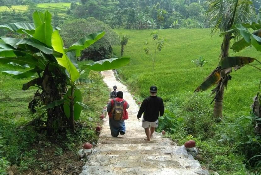 Sejumlah warga melintasi jalan menuju makam pahlawan nasional Tan Malaka yang terletak di Desa Selopanggung, Kecamatan Semen, Kediri, Selasa (21/2).