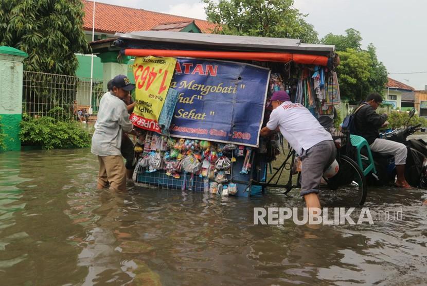Sejumlah warga melintasi jalan yang terimbas banjir, Kamis (15/2).