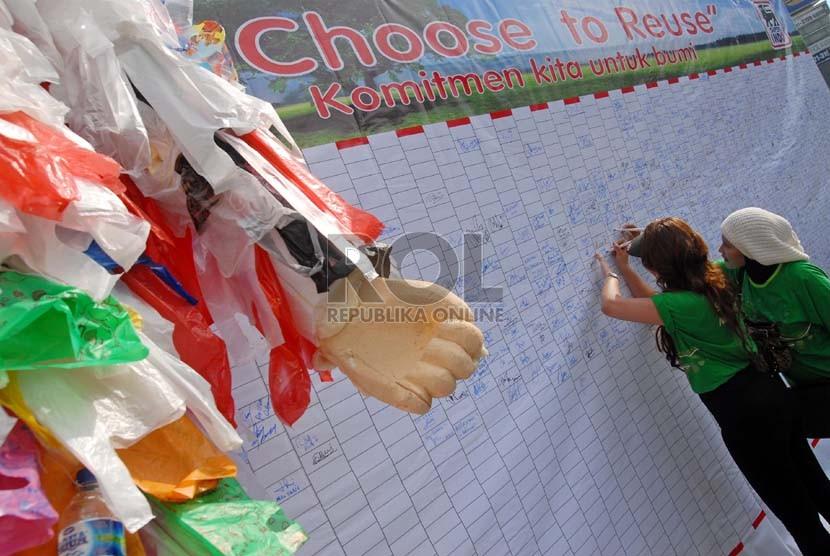 Sejumlah warga menandatangani spanduk dukungan pengurangan sampah kantong plastik di Jalan Jenderal Sudirman, Jakarta, Ahad (24/2).  (Republika/Agung Fatma Putra)