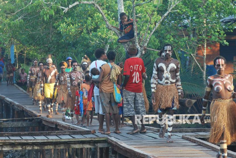 Sejumlah warga Suku Asmat berjalan disebuah perempatan jalan yang terbuat dari papan di Kabupaten Asmat Propinsi Papua