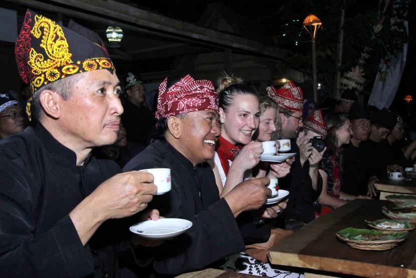 Sejumlah wisatawan asing menikmati kopi gratis saat menghadiri Festival Ngopi Sepuluhewu (Sepuluh ribu Kopi) di Kemiren, Banyuwangi, Jawa Timur, Sabtu (5/11).