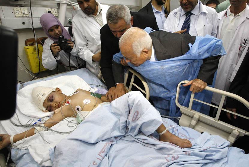 Sekjen Liga Arab Nabil Elaraby didampingi Perdana Menteri Palestina Ismail Haniyeh saat menjenguk seorang anak Palestina yang terluka dalam serangan udara Israel di sebuah rumah sakit di Gaza,Selasa (20/11). (AP Pool/Ahmed Zakot)
