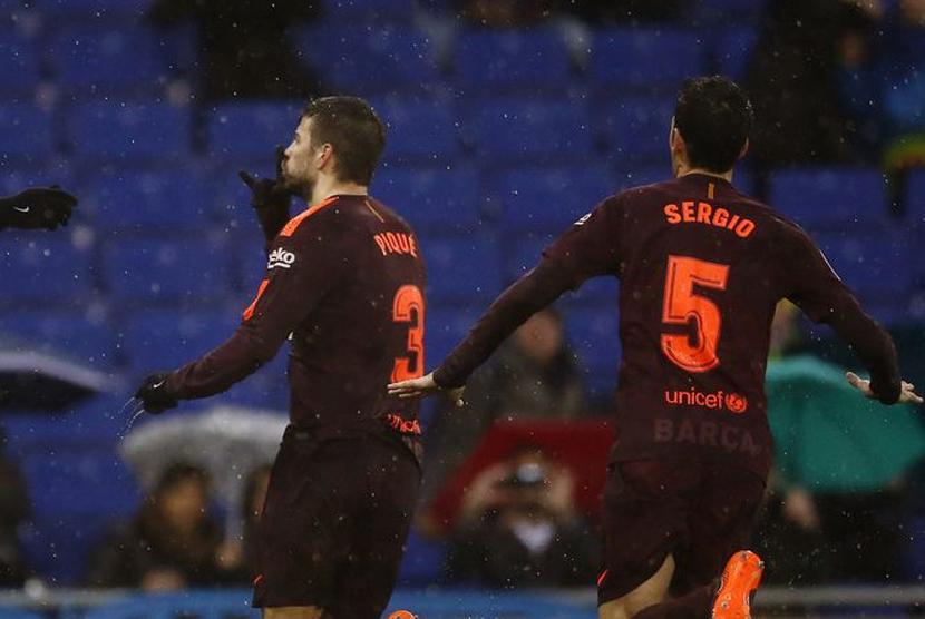 Selebrasi Pique usai mencetak gol ke gawang Espanyol, Ahad (4/1).