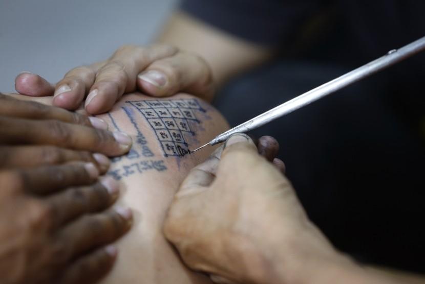 Seniman tato sedang membuat tato.