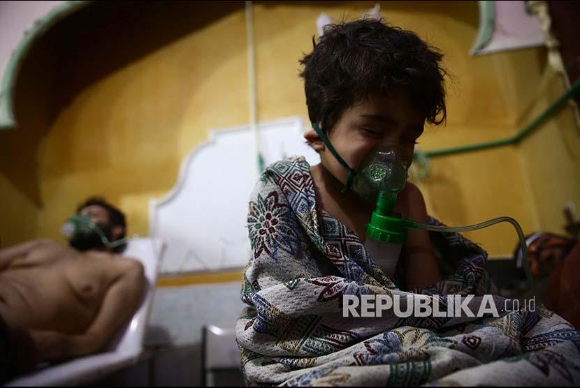 Seorang anak dan pria memperoleh penanganan medis setelah terpapar gas beracun di  Douma, Ghouta Timur, Damascus, Syria, Ahad (25/2).