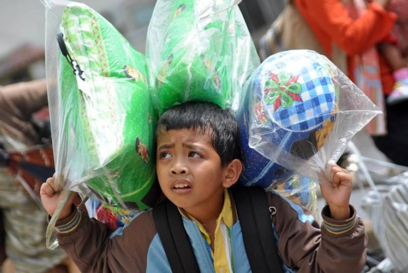 Seorang anak dari peserta transmigrasi asal DI Yogyakarta membopong barang bawaan, sesaat setelah turun dari KM Leuser jurusan Semarang-Pontianak, di Pelabuhan Dwikora, Pontianak, Kalbar