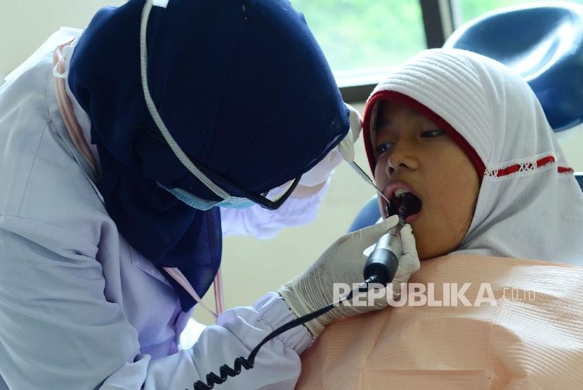 Seorang anak diperiksa giginya.
