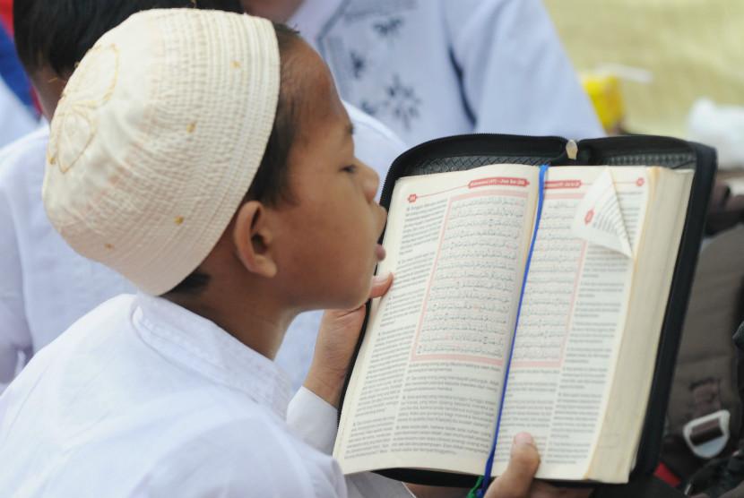 Seorang anak membaca Alquran dalam kegiatan khataman secara massal menyambut Ramadhan di Lapangan Tugu Proklamasi, Jakarta, Kamis (19/7). (Aditya Pradana Putra/Republika)