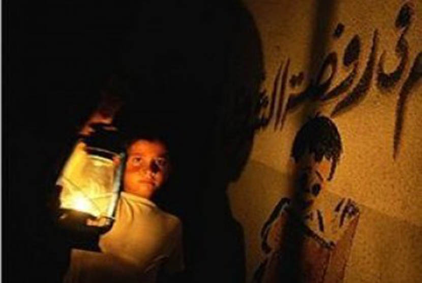 Seorang anak membawa lentera dalam krisis listrik di Gaza.