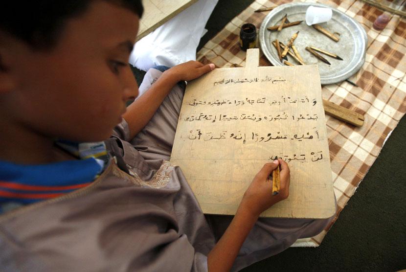 Seorang anak membaca sebuah papan tulis kayu sambil menghafal Alquran di Tripoli, Libya, Senin (23/7).   http://asalasah.blogspot.com/2013/06/berusaha-menghafal-al-quran-menggunakan-papan-kayu.html