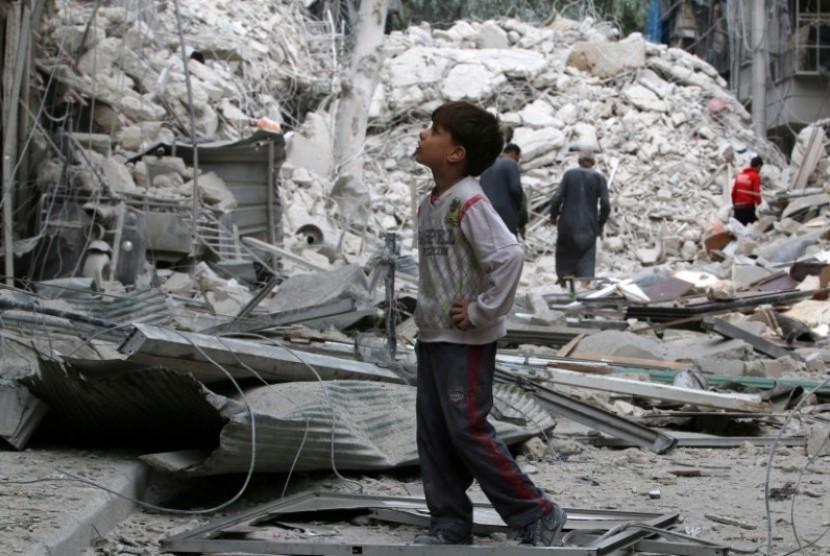 Seorang anak menyaksikan bangunan bekas pengeboman di  Suriah (Ilustrasi)