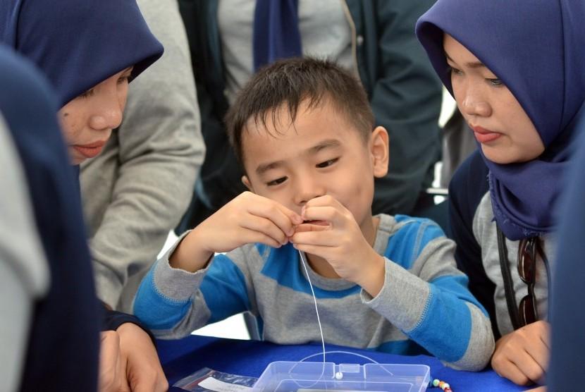Seorang anak penderita autisme merangkai manik-manik untuk di jadikan gelang pada kampanye kegiatan Hari Peduli Autis Internasional di Anjungan Losari, Makassar, Sulawesi Selatan, Minggu (2/4).