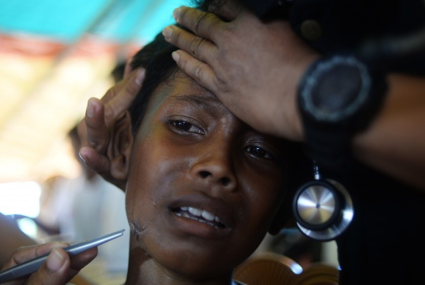 Seorang anak pengungsi Rohingya diperiksa lukanya oleh tenaga medis di tenda kesehatan Indonesia, Kamp Pengungsian Jamtoli, Cox Bazar, Bangladesh, Minggu (1/10).