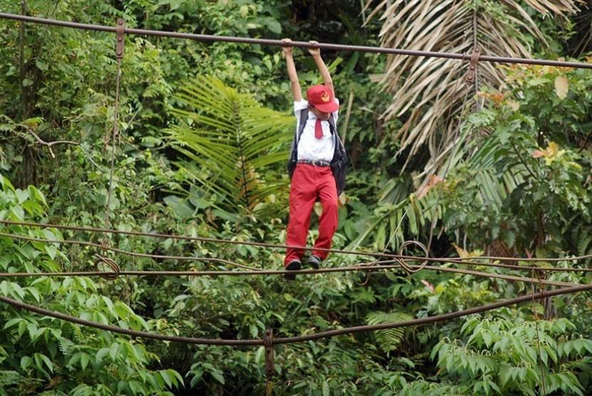 Seorang anak Sekolah Dasar di Padang, Sumatera Barat harus meniti tali jembatan yang rusak ini untuk menuju ke sekolah.
